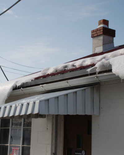 jalco snowguards red metal roof with snowguards and snow closeup - snow sliding and snowguards