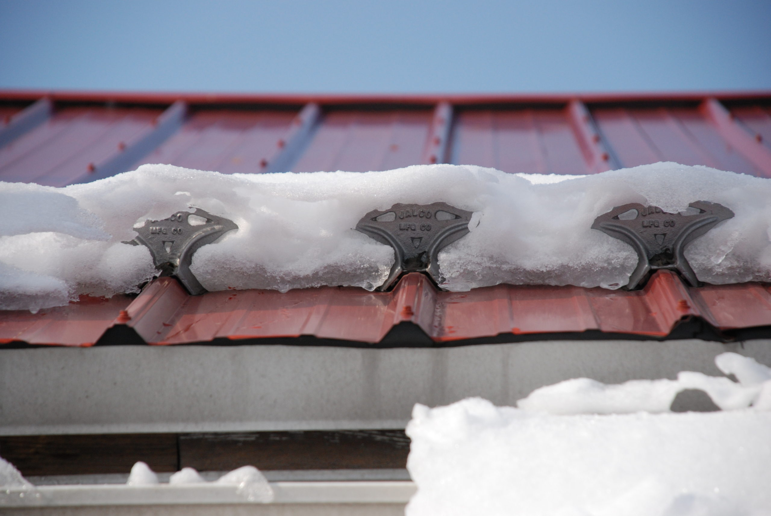 jalco snowguards red metal roof with snowguards and snow closeup